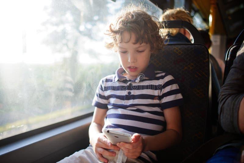Ein kleiner Passagier eines Stadtbusses mit einem Smartphone in der Hand stockfoto
