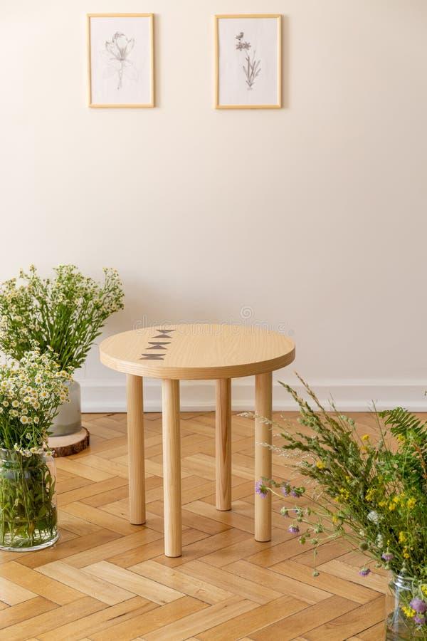 Ein kleiner runder Holztisch, der durch frische Wiese umgeben wird, blüht Stellung auf einem Parkett gegen eine helle beige Wand  lizenzfreies stockbild