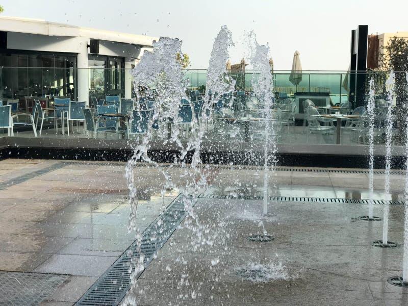 Ein kleiner schöner Gesangbrunnen im Freien, auf der Straße Wassertropfen, Wasserstrahlen im Flug eingefroren in der Luft wieder stockfotos