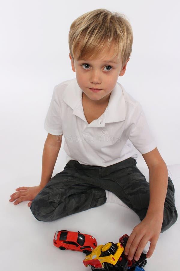 Ein kleiner spielerischer Junge, der mit Autospielwaren auf seinen Knien spielt lizenzfreies stockbild