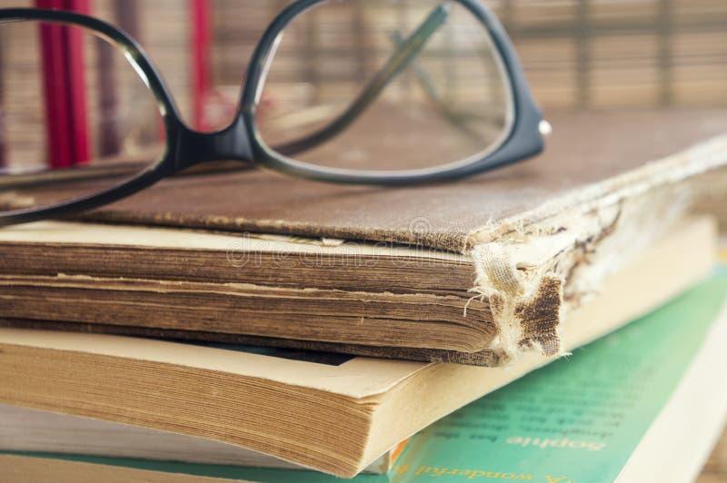 Ein kleiner Stapel alte Bücher, Gläser Warme Weinlesefarben lizenzfreies stockfoto