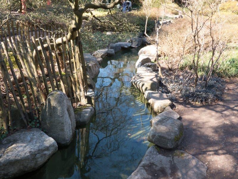 Ein kleiner Strom im asiatischen Garten mit Steinen auf dem Rand lizenzfreie stockbilder