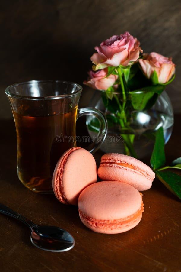 ein kleiner transparenter Becher schwarzer Tee mit buschigen rosa Rosen in einem Vase und rosa in Makronenkuchen auf einem dunkle stockbilder