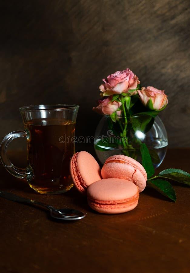 ein kleiner transparenter Becher schwarzer Tee mit buschigen rosa Rosen in einem Vase und rosa in Makronenkuchen auf einem dunkle lizenzfreie stockbilder