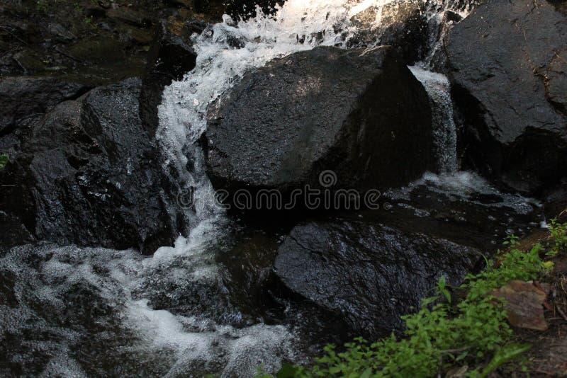 Ein kleiner weiß-weicher Wasserfall, der scharfe Struktur von enormen dunklen Felsen umfasst lizenzfreies stockfoto