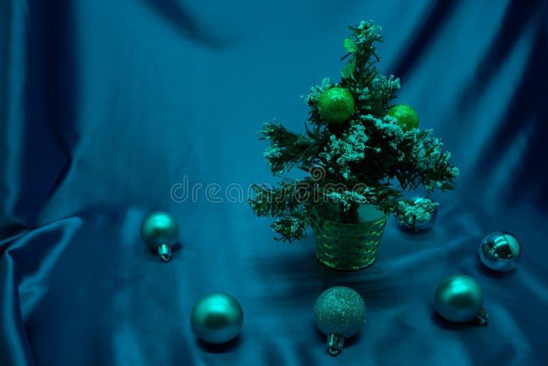 Ein kleiner Weihnachtsbaum in einem Topf, verziert mit Bällen, Girlanden und Lichtern lizenzfreie stockfotografie