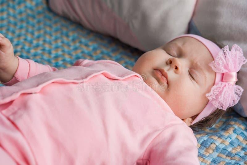 Ein kleines Baby liegt auf einem Bett lizenzfreies stockbild