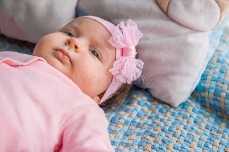 Ein kleines Baby liegt auf einem Bett lizenzfreie stockbilder