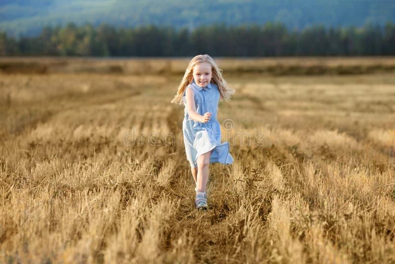 Ein kleines blonde Mädchen läuft im Sommer auf einem Weizenfeld lizenzfreies stockbild