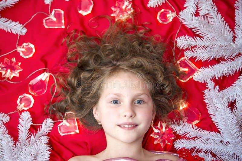 Ein kleines blondes Mädchen, das auf einem roten Boden mit einer Weihnachtsgirlande und Tannenzweigen um ihren Kopf liegt stockfotografie
