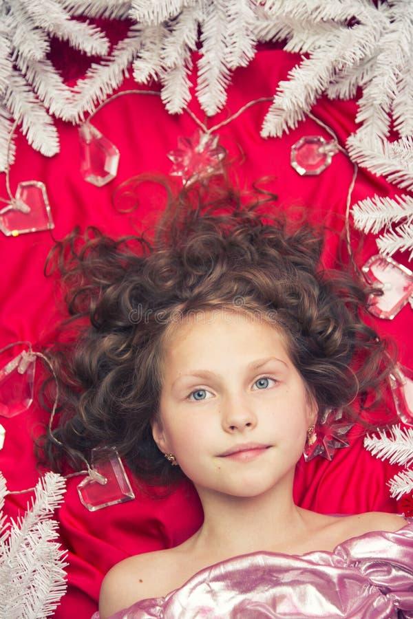 Ein kleines blondes Mädchen, das auf einem roten Boden mit einer Weihnachtsgirlande und Tannenzweigen um ihren Kopf liegt lizenzfreies stockbild
