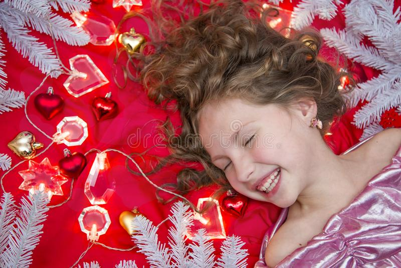 Ein kleines blondes Mädchen, das auf einem roten Boden mit einer Weihnachtsgirlande und Tannenzweigen um ihren Kopf liegt stockbilder
