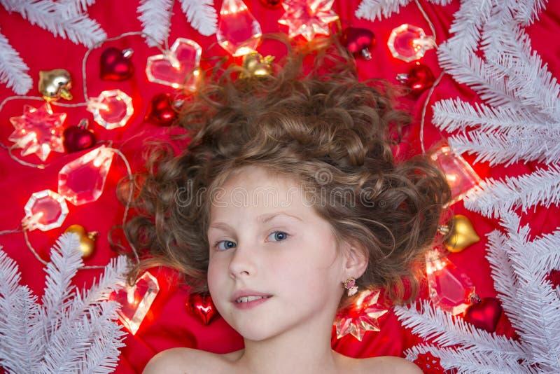 Ein kleines blondes Mädchen, das auf einem roten Boden mit einer Weihnachtsgirlande und Tannenzweigen um ihren Kopf liegt lizenzfreies stockfoto