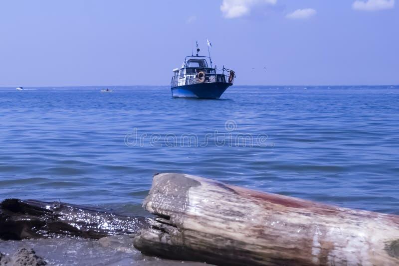 Ein kleines Boot ist im blauen Meer stockfotografie