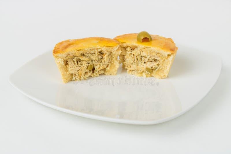 Ein kleines brasilianisches Hühnertorten-Gebäck geschnitten zur Hälfte Empadinha lizenzfreies stockbild