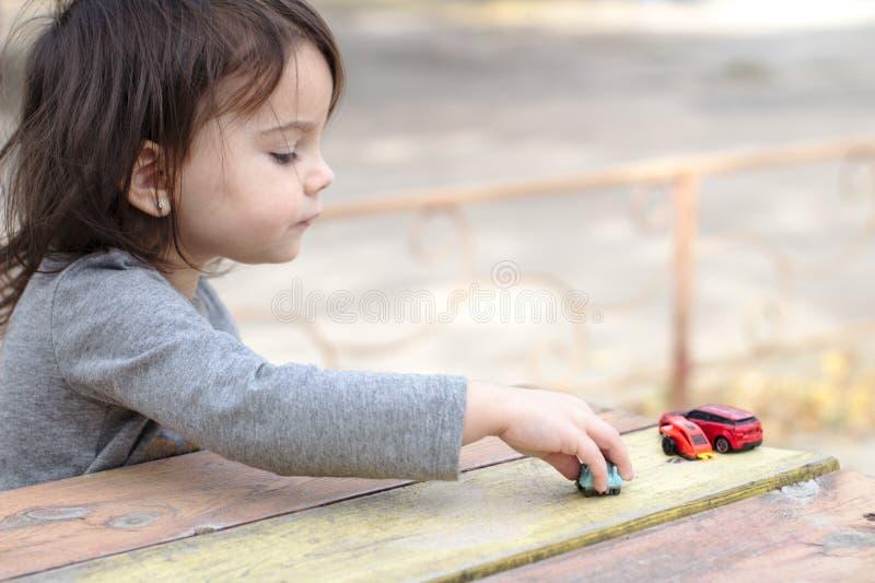 ein kleines children& x27; s-Handpunkte zu einem Spielzeugauto unter einer Vielzahl Autos auf einer hölzernen rot-gelben Tabelle lizenzfreie stockfotografie