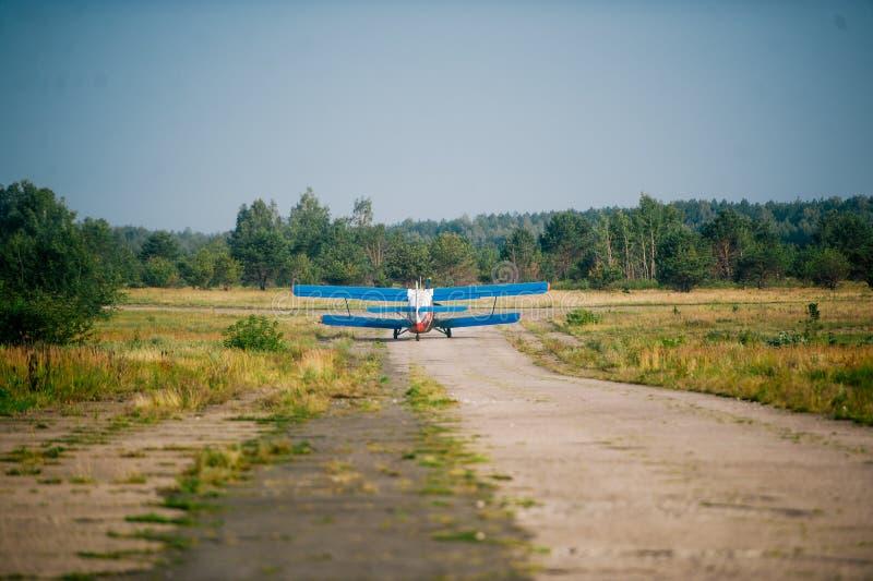 Ein kleines Flugzeug, das auf einem Gras, Landrollbahn in einem szenischen Standort sich entfernt stockfoto