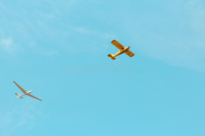 Ein kleines gelbes Flugzeug- und Segelflugzeugfliegen über dem blauen Himmel lizenzfreies stockfoto