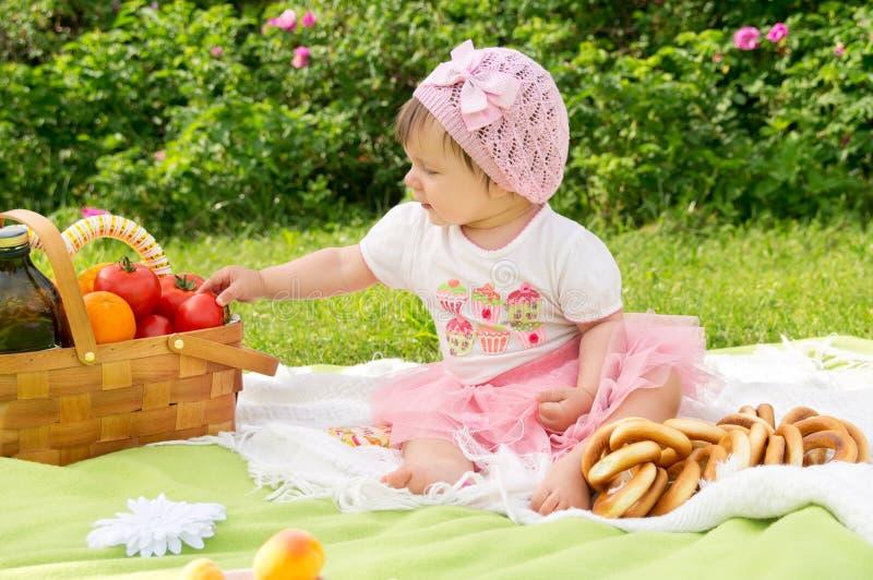Ein kleines Kind, das auf einem Picknick stillsteht lizenzfreie stockfotografie