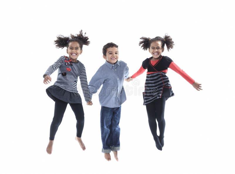 Ein kleines Kind des netten Afroamerikaners springen lokalisiert stockfoto