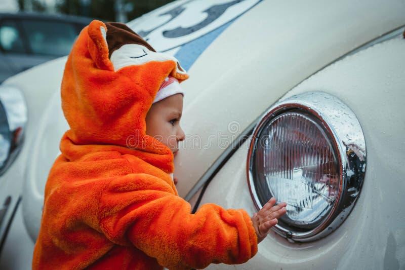 Ein kleines Kind in einem Fuchskostüm steht nahe einem wieder hergestellten alten Auto und überprüft es mit Interesse Baby im kig stockbilder