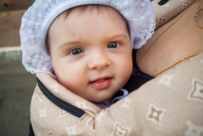 Ein kleines Kind in einem Kind-` s Rucksack mit Mutter Hälfte ein jähriges Baby Weg hinunter die Straße lizenzfreies stockfoto