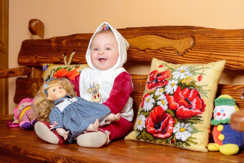 Ein kleines Kind in einem Schal, der auf einem Sofa mit gestickten Kissen sitzt stockfotos