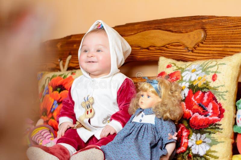 Ein kleines Kind in einem Schal, der auf einem Sofa mit gestickten Kissen sitzt stockbild