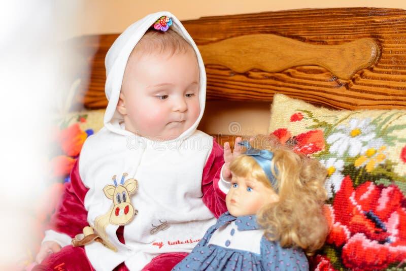 Ein kleines Kind in einem Schal, der auf einem Sofa mit gestickten Kissen sitzt stockbilder