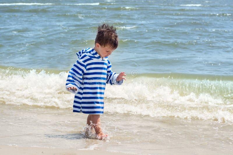 Ein kleines Kind in einer gestreiften Robe steht auf der Küste im Wasser und betrachtet seine nassen Beine, um die Welt zu kennen lizenzfreie stockbilder