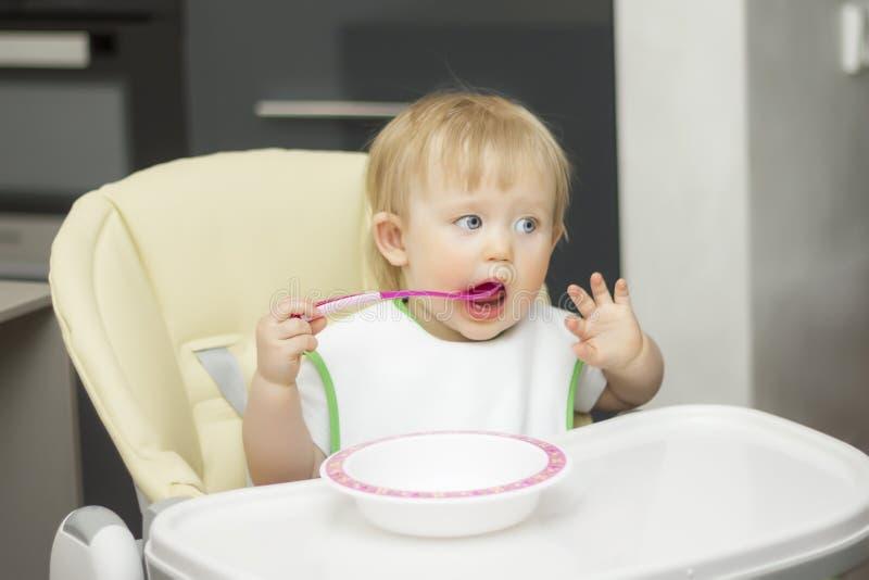 Ein kleines Kind isst mit einem Löffel von einer Platte, sitzt auf einem Highchair lizenzfreie stockbilder