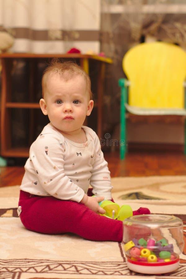 ein kleines Kind sitzt auf dem Boden im Raum und spielt mit Ohrstöcken stockfotografie