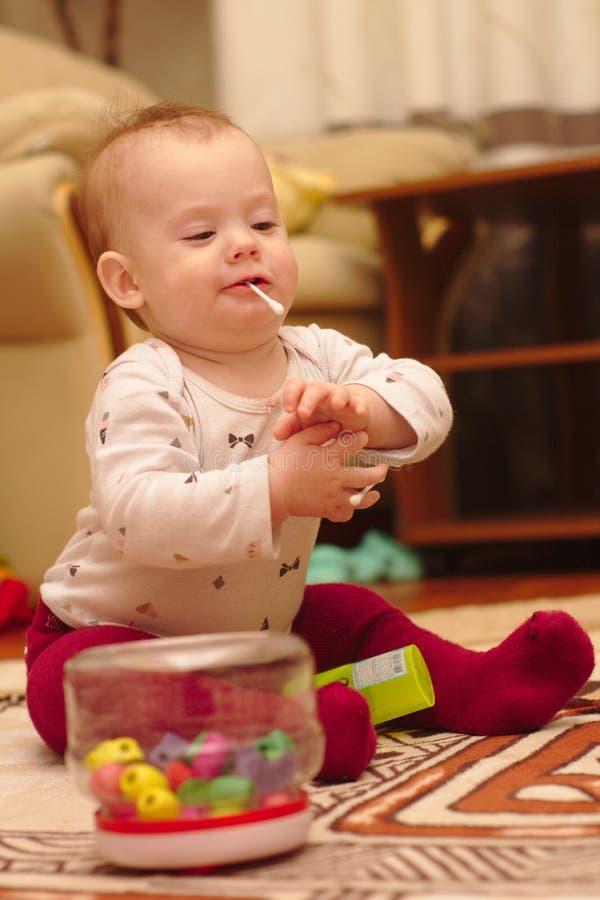 ein kleines Kind sitzt auf dem Boden im Raum und spielt mit Ohrstöcken stockfoto