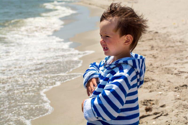 Ein kleines Kind steht auf der schauenden und lächelnden Küste lizenzfreies stockfoto