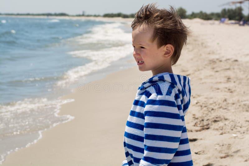 Ein kleines Kind, welches das Meer betrachtet die Wellen bereitsteht, stockfoto