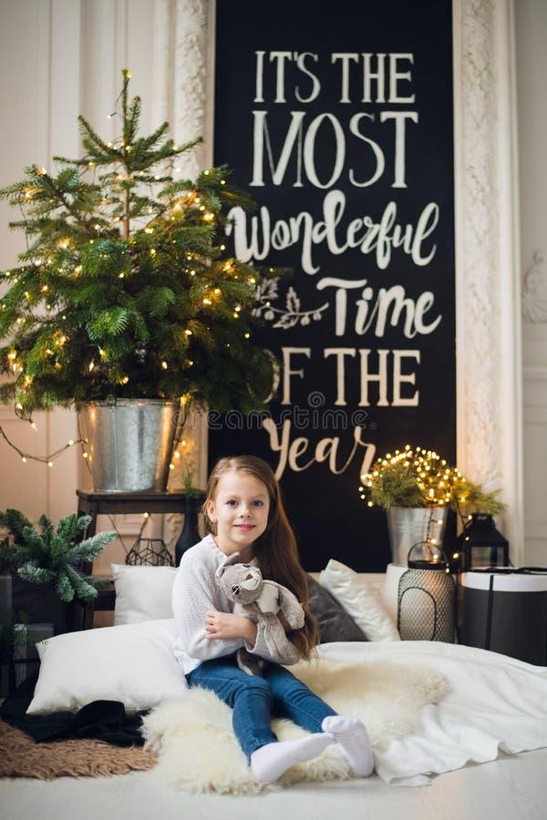 Ein kleines lächelndes Mädchen, das ein kleines lila Häschenspielzeug in ihren linkshänden hält und in der Weihnachtsdekoration s stockfotografie