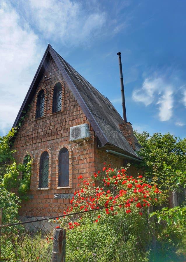 Ein kleines Landhaus mit einem blühenden Blumenbeet stockfotografie