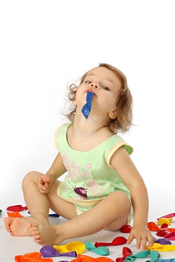 Ein kleines Mädchen bläst Ballone auf. lizenzfreie stockfotografie