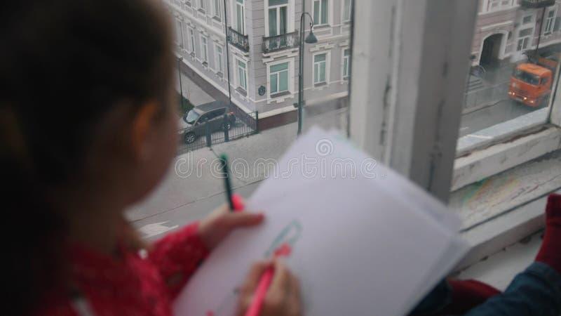 Ein kleines Mädchen, das auf dem Fensterbrett und dem Zeichnen, lächelnd auf dem backround der Stadt sitzt Fokus auf Händen stockbilder
