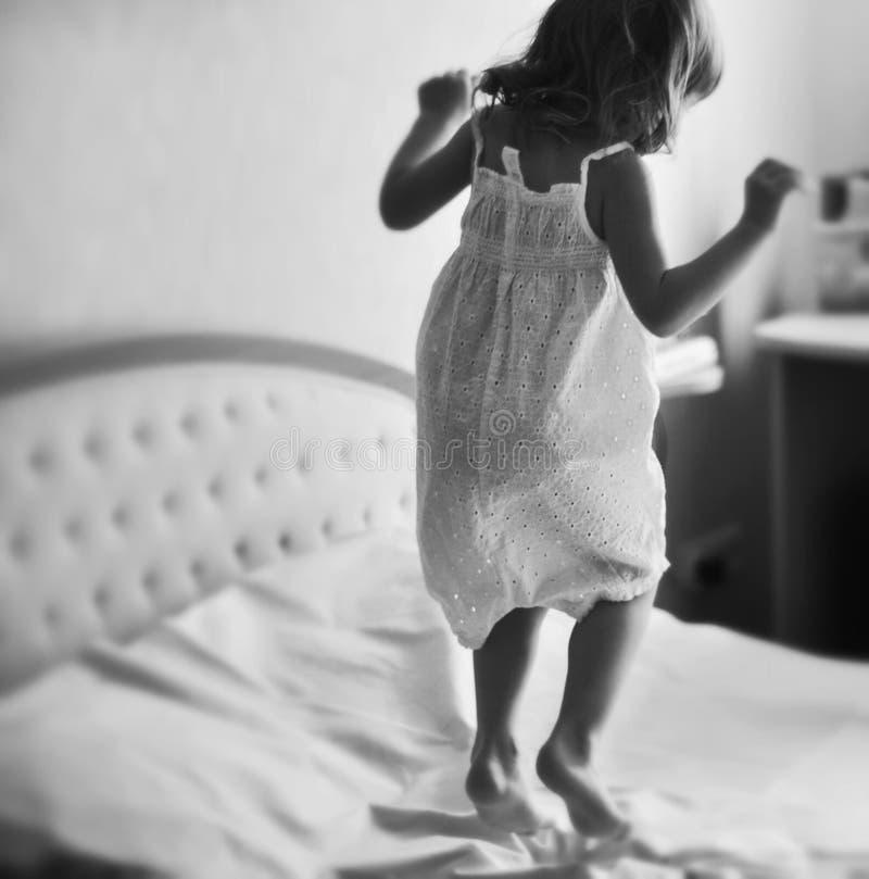 Ein kleines Mädchen, das auf ein Königgrößenbett springt lizenzfreies stockfoto