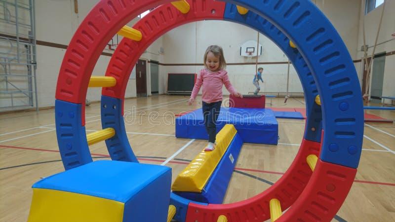Ein kleines Mädchen, das auf einem Gymnastikstrahl balanciert lizenzfreies stockbild