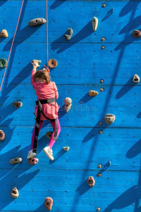 Ein kleines Mädchen, das auf einer vertikalen Wand klettert lizenzfreie stockfotos