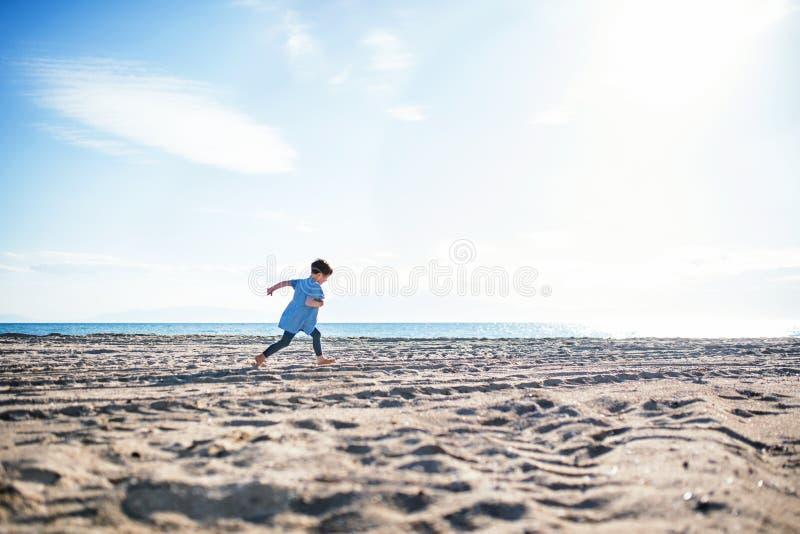 Ein kleines Mädchen, das draußen auf Sandstrand läuft Kopieren Sie Platz lizenzfreie stockfotografie