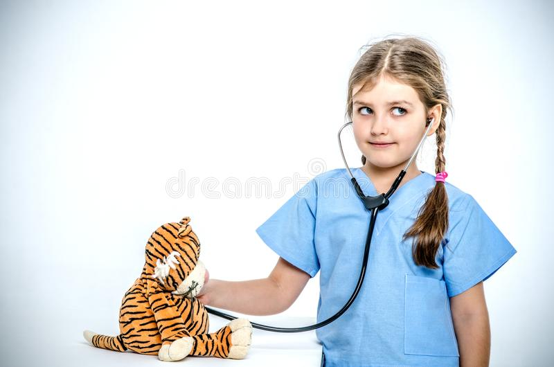 Ein kleines Mädchen, das in einer chirurgischen Klage gekleidet wird, hört auf ihren Spielzeugtiger mit einem phonendoscope lizenzfreies stockbild