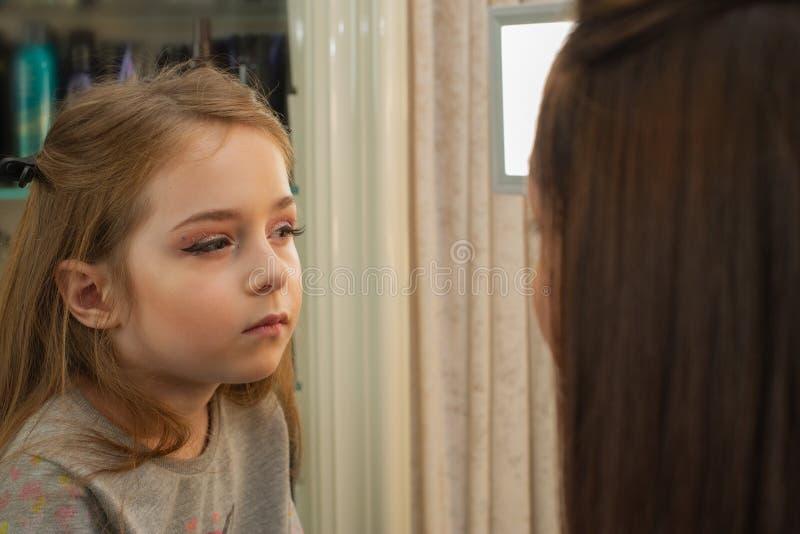 Ein kleines Mädchen, das Make-up vor der Ausführung am Stadium tut Vorbereitung vor der Leistung in der Umkleidekabine stockfotos