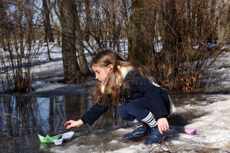 Ein kleines Mädchen, das mit Papierbooten in halb-gefrorenen Pfützen des Vorfrühlings spielt lizenzfreies stockbild