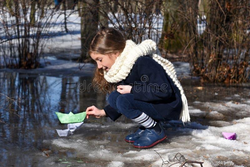 Ein kleines Mädchen, das mit Papierbooten in halb-gefrorenen Pfützen des Vorfrühlings spielt stockfoto