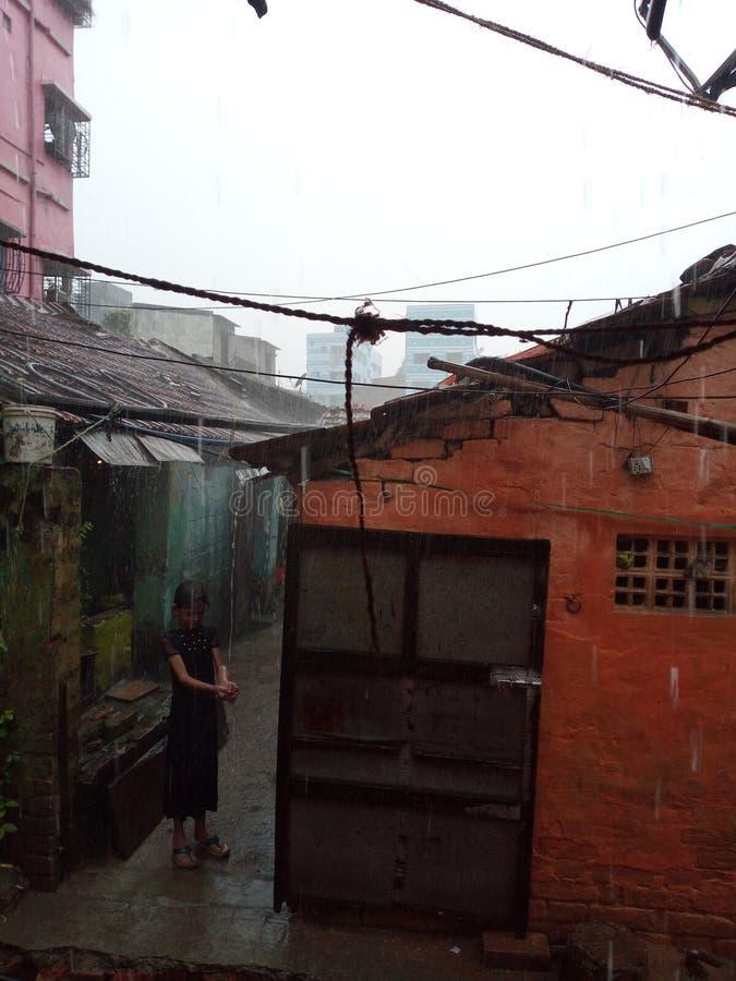 Ein kleines Mädchen, das Spaß mit dem Regnen tut stockfotos