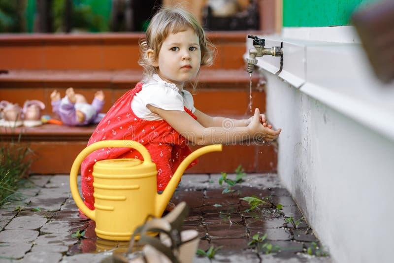 Ein kleines Mädchen, das in sundress gekleidet wird, hält ihre Hände unter dem laufenden Leitungswasser, das nahe bei der Gießkan lizenzfreie stockfotografie
