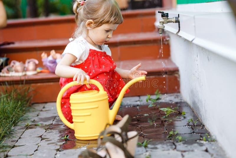 Ein kleines Mädchen, das in sundress gekleidet wird, zeichnet Wasser in einer Gießkanne im Garten nahe bei dem Haus am Sommertag stockbild